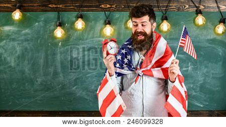 Man With Beard On Cheerful Face Holds Flag Of Usa And Clock, Chalkboard On Background, Copy Space. A