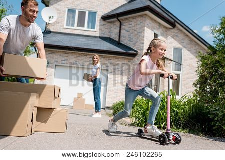 Little Kid Riding On Kick Scooter And Her Parents Unpacking Cardboard Boxes For Relocation Into New