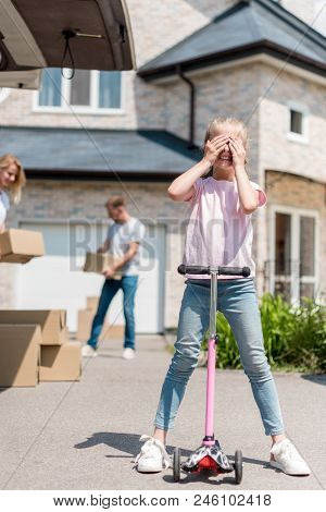 Little Kid Covering Eyes On Kick Scooter And Her Parents Unpacking Cardboard Boxes For Relocation In