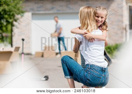 Rear View Of Woman Hugging Smiling Daughter And Man Unpacking Cardboard Boxes Behind In Yard Of New