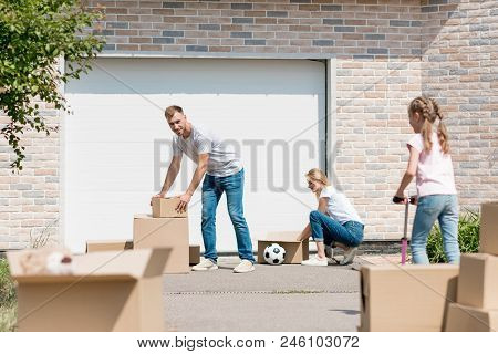 Young Couple Unpacking Cardboard Boxes While Their Daughter Riding On Kick Scooter In Front Of New C