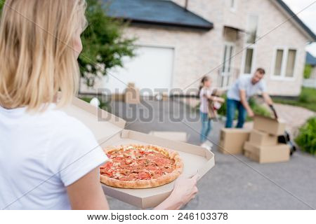 Partial View Of  Woman Holding Pizza While Her Husband And Daughter Unpacking Cardboard Boxes In Fro