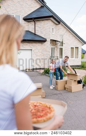 Cropped Image Of Woman Holding Pizza While Her Husband And Daughter Unpacking Cardboard Boxes In Fro
