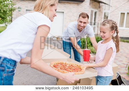 Smiling Mother Holding Box With Pizza And Daughter Taking Slice Of Pizza While Father Unpacking Card