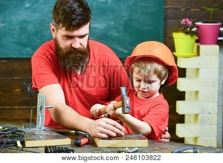 Handyman Concept. Father With Beard Teaching Little Son To Use Tools, Hammering, Chalkboard On Backg
