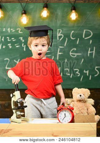 Child, Pupil On Shocked Face Near Microscope. Kid Boy In Graduate Cap Near Microscope In Classroom,