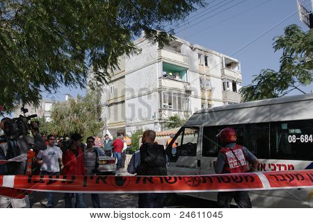 ASHKELON - JANUARY 10: Residents of apartment building and soldiers from the rescue team in front of the damaged building short time after missile hit it on January 10, 2009 in Ahskelon, Israel.