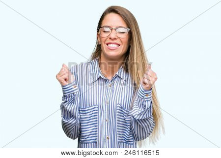 Beautiful young woman wearing elegant shirt and glasses excited for success with arms raised celebrating victory smiling. Winner concept.