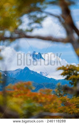 Snow capped mountain covered with clouds and lush trees on the foreground. Patagonia, Chile