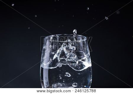 Glass Of Water On A Gray Background With Drops In Different Directions