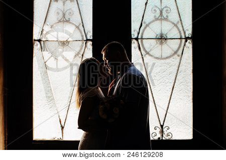 portrait of a romantic couple in a backlight from a window or door, silhouette of a couple in a doorway with a backlight, couple of lovers groom and bride at the window, girl holding flowers in hands. poster