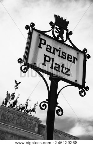 closeup of a nameplate in the street with the name ot the Pariser Platz in Berlin, Germany, with the Brandenburg Gate in the background, in black and white