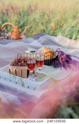 Picnic Outdoors With Wine, Fruits And Croissants, Strawberry, Cherry, Wine, Croissants And Basket In