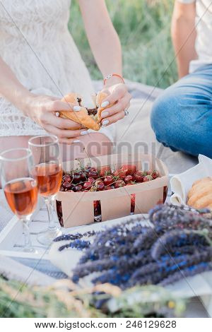 Couple In Love Are Having Summer Picnic Outdoors With Wine, Fruits And Croissants, Strawberry, Cherr