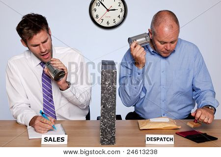 Photo showing the behind the scenes reality of the sales and despatch departments for a small business, both guys sharing the same desk and communicating via a tin can phone.