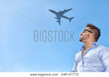 A bearded man in front of a blue sky with an airplane
