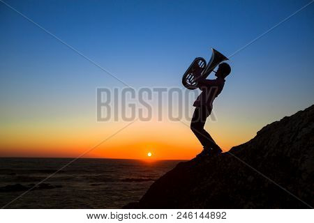 Silhouette of the musician play Tuba on the ocean coast at amazing sunset.