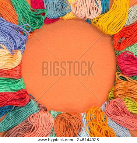 Lots of knitting wool samples on an orange textured paper background with copy space in the middle.