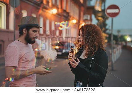 Loving Couple Of Hipsters On Date. Guy In Hat And T-shirt Is Holding Electronic Cigarette In His Han