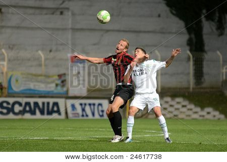 KAPOSVAR, HUNGARY - OCTOBER 15: Benjamin Balazs (in white) in action a Hungarian National Championship soccer game - Kaposvar (white) vs Honved (red) on October 15, 2011 in Kaposvar, Hungary.