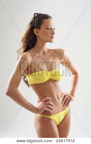 Stock photo of young, fit and sexy woman in yellow swimsuit