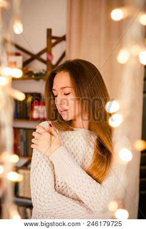 Young Woman Standing Near Yellow Twinkling Garlands In Room. Concept Of Celebrating New Year And Chr