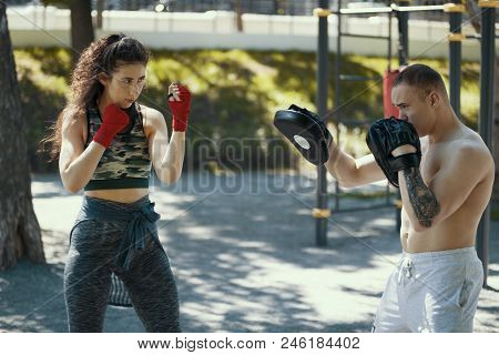 Boxers - Muscular Man And Young Woman Engaged In Boxing In The Park Ar Sunny Day, Horizontal