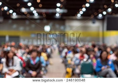 Abstract Blurred Photo Of Conference Hall Or Seminar Room In Exhibition Center With Speakers On The