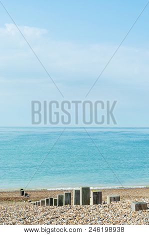Pebble Beach Scene Of Calm Sea On Bright Day. Wooden Posts Of Varying Heights Lead Towards The Shore
