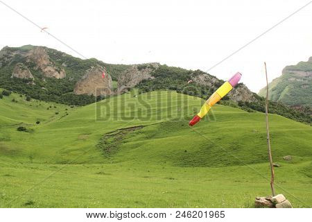 Paradrom Chegem Green Hills And Mountains, Paragliders In The Sky And A Stick With A Striped Multi-c