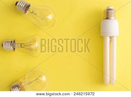 Energy-saving Lamp Vs. Incandescent Lamps. The Concept Of Energy Saving . On A Yellow Background.one