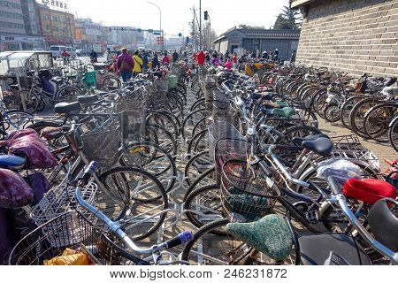 Beijing, China - March 14, 2016: Bicycles, Scooters And Cars In Beijing Streets.  Bicycle Parking.