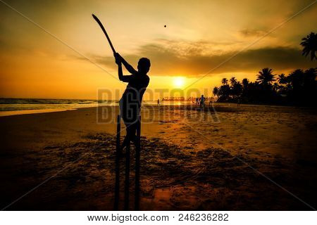 boy playing cricket at sunset on tropical beach - national sport in Sri Lanka