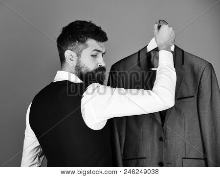 Consumerism And Elegance Concept. Man With Beard In Vest With Jacket. Shop Assistant Or Seller Holds