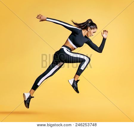 Sporty Woman Runner In Silhouette On Yellow Background. Photo Of Attractive Woman In Fashionable Spo