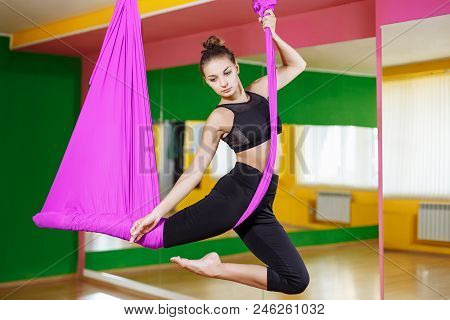 Young Beautiful Girl Practicing Aerial Yoga In Gym.