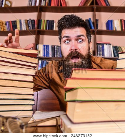 Man On Shocked Face Between Piles Of Books, While Studying In Library, Bookshelves On Background. De
