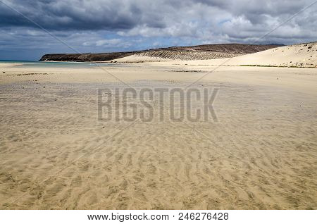 Low Tide On Sotavento Beach On Fuerteventura, Canary Islands With Stormy Dramatic Sky And Water Trai