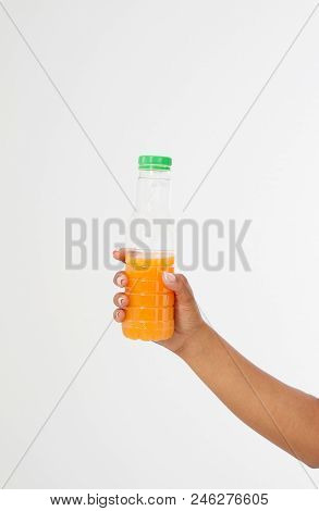 Black Hand Holding A Bottle Of Juice Isolated On A White Background. Front View. Mock Up. Copy Space