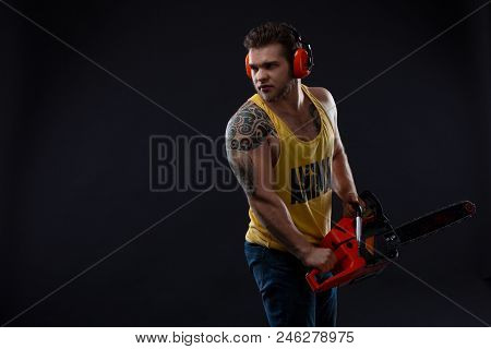 Male Construction Worker With Tattoo With Chainsaw. Portrait Of A Strong Muscular Man. Young Handsom