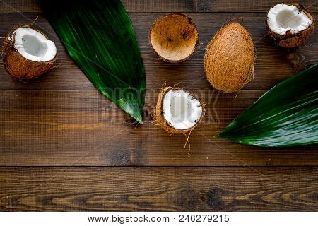 Tropical Composition With Coconut. Whole Coconuts And Coconut Cut In Half Near Pulm Leaves On Dark W