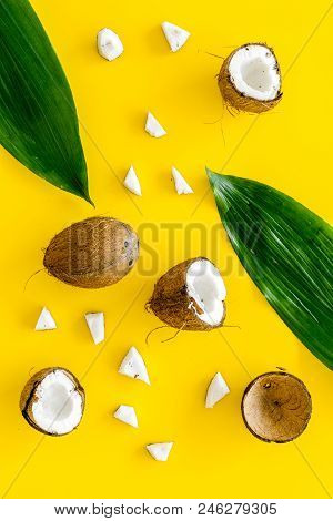 Coconut Background. Whole And Cut Coconuts, Pulp And Palm Leaves On Yellow Background Top View.