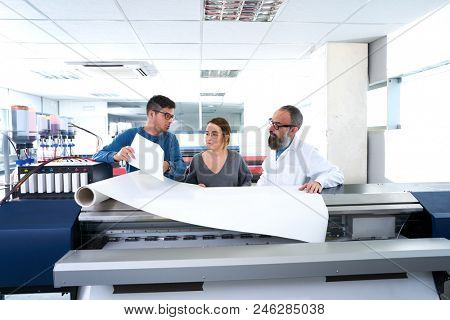 Printing team at industry plotter printer men and woman