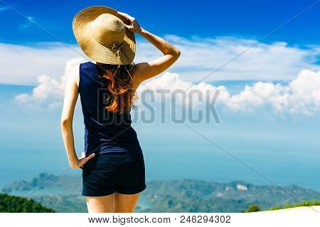 Young Traveling Woman Wearing Hat And Standing On The Top Of The Mountain Cliff And Watching Beautif