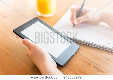Girl Is Reading Ebook On Digital Tablet Device And Is Taking Notes