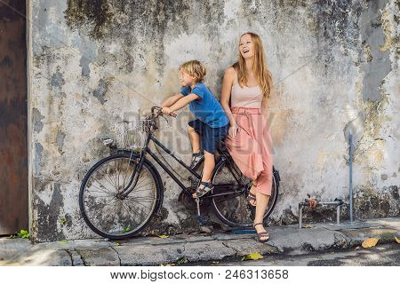 Mother And Son On A Bicycle. Public Street Art Name Children On A Bicycle Painted 3D On The Wall Tha