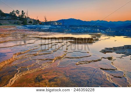 Mammoth Hot Springs in one of the most popular geothermal attractions in Yellowstone National Park in Wyoming.  Sunrise light creates a beautiful glow on the water and the mountains.