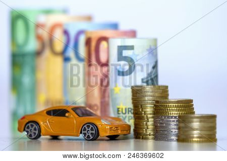 Blurred Row Of Rolled Hundred, Fifty, Twenty, Ten And Five New Euro Banknotes And Pile Of Coins With