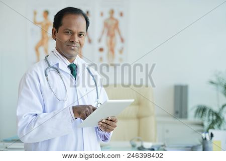 Portrait Of Indian Doctor Using Touchpad For Work