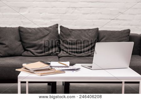 Freelancer Workplace With Laptop And Notepads On Table At Living Room
